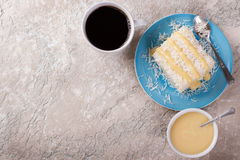 Brazilian traditional dessert: sweet couscous tapioca pudding. Cuscuz doce with coconut on plate with cup of coffee on marble table. Selective focus. Copy space Stock Photography