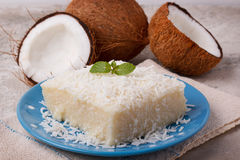 Brazilian traditional dessert: sweet couscous tapioca pudding. Cuscuz doce with coconut on plate on marble table. Selective focus Royalty Free Stock Image