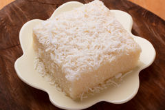 Brazilian traditional dessert: sweet couscous tapioca pudding. Cuscuz doce with coconut on wooden board. Selective focus Stock Image