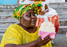 Brazilian woman of African descent offering `Cocada`. Its a Brazilian dessert made of coconut. BAHIA, BRAZIL - CIRCA JAN 2016: Brazilian woman of African descent Stock Photo