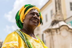 Brazilian woman of African descent wearing traditional clothes from the state of Bahia in the old colonial district of Salvador. Pelourinho Stock Image