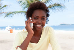Brazilian woman at beach laughing at phone Royalty Free Stock Images