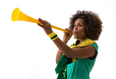 Brazilian woman blowing by vuvuzela on white background Stock Photography