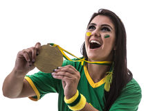 Brazilian woman fan showing a gold medal on white background Royalty Free Stock Photo