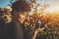 Brazilian woman with retro camera in park stock photos
