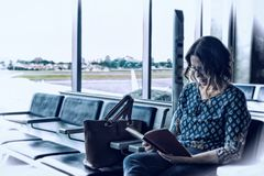 Brazilian woman sat and reading a book. Brazilian woman sat, waiting and reading a book in the airport stock photography
