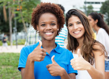 Brazilian woman showing thumb up with mexican girl. Brazilian women showing thumb up with mexican girl outdoor in the city Stock Image