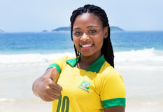 Brazilian woman in a soccer jersey at beach showing thumb Royalty Free Stock Photos