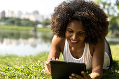 Brazilian woman using tablet computer in the park Stock Photo