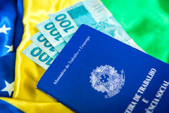 Brazilian work document and social security document (Carteira de Trabalho) and brazilian currency (Reais) on brazilian flag Royalty Free Stock Photography