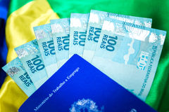 Brazilian work document and social security document (Carteira de Trabalho) and brazilian currency (Reais) on brazilian flag Royalty Free Stock Photo