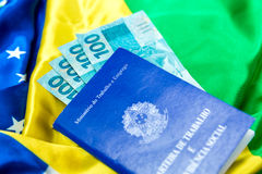 Brazilian work document and social security document (Carteira de Trabalho) and brazilian currency (Reais) on brazilian flag Royalty Free Stock Image