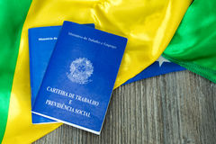 Brazilian work document and social security document on the table (Carteira de Trabalho) on brazilian flag Stock Image