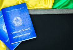 Brazilian work document and social security document on the table (Carteira de Trabalho) on brazilian flag Royalty Free Stock Image