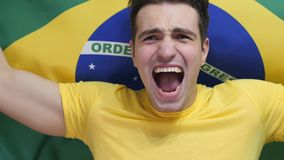 Brazilian Young Man Celebrates holding the flag of Brazil in Slow Motion. High quality stock photo