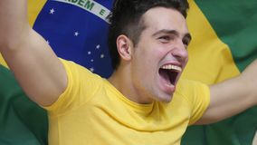 Brazilian Young Man Celebrating while holding the flag of Brazil in Slow Motion. High quality royalty free stock photo