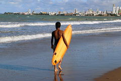 Brazilian young man walking along the cost with surfboard under his arm. Young man is walking along the cost, carrieng his orange surfboard under the  arm Royalty Free Stock Image