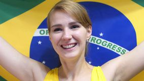 Brazilian Young Woman Celebrating while holding the flag of Brazil in Slow Motion. High quality royalty free stock photo