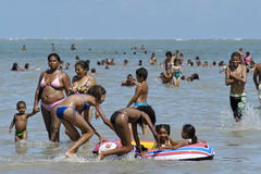 Brazilians have water fun in Atlantic Ocean, Sea. In the city Recife, Brazil, it can be very crowded on the beach on a sunday. A lot Brazilian families, old and Royalty Free Stock Photo