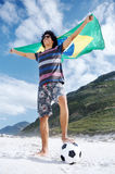 Brazillian soccer man. Latino Brasil football soccer fan with flag and ball on beach Royalty Free Stock Photos