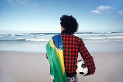 Brazillian soccer man. Latino Brasil football soccer fan with flag and ball on beach Stock Images