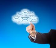 Brazo corporativo que alcanza en el enjambre de la nube de correos electrónicos Imagenes de archivo