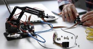 Brazo del robot de programación del ingeniero de la robótica para el proyecto de la automatización almacen de video