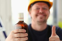 Brazo del trabajador borracho en casco amarillo foto de archivo