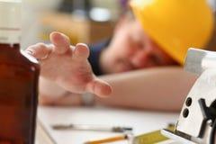 Brazo del trabajador borracho en casco amarillo imagenes de archivo
