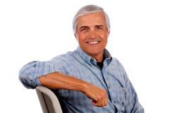 Brazo envejecido medio feliz del hombre en la parte posterior de la silla imagen de archivo libre de regalías