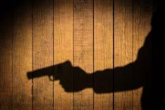 Brazo extendido con un arma. Sombra negra en fondo de madera. Fotos de archivo libres de regalías