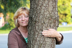 Brazo maduro sonriente de la mujer alrededor del árbol Imágenes de archivo libres de regalías