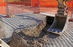 Brazo mecánico del cavador en las obras por carretera confinadas por la naranja Fotos de archivo libres de regalías