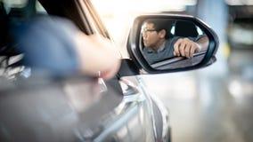 Brazo que se inclina del hombre asiático del conductor fuera de la ventanilla del coche imagenes de archivo