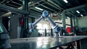 Brazo robótico automatizado que trabaja en una planta metrajes