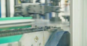 Brazo robótico en una cadena de producción de las piezas para la industria del automóvil almacen de metraje de vídeo