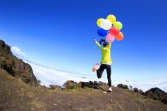 Brazos abiertos alegres de la mujer joven con los globos Foto de archivo libre de regalías