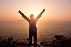 Brazos abiertos de la mujer agradecida a la salida del sol Fotografía de archivo