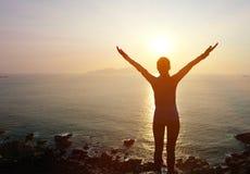 Brazos abiertos de la mujer agradecida a la salida del sol Imagen de archivo