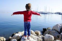 Brazos abiertos de la niña que miran el mar del azul del puerto deportivo Imagen de archivo