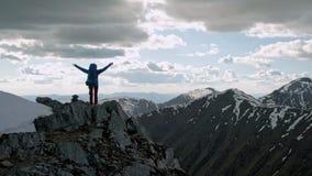 Brazos abiertos del backpacker acertado de la mujer joven en pico de montaña almacen de video