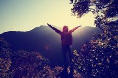 Brazos abiertos del caminante de la mujer joven en pico de montaña Imágenes de archivo libres de regalías