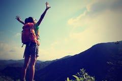 Brazos abiertos del caminante de la mujer joven a la salida del sol en pico de montaña Foto de archivo libre de regalías