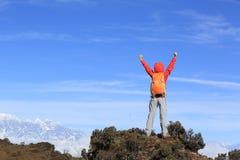 Brazos abiertos del caminante del Backpacker en el pico de montaña hermoso Imagen de archivo libre de regalías