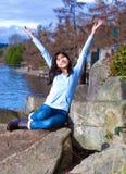 Brazos adolescentes jovenes de la muchacha aumentados mientras que se sienta en roca grande a lo largo de la orilla del lago, fel Fotos de archivo