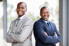 brazos africanos de los hombres de negocios cruzados foto de archivo