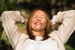 Brazos al aire libre de la mujer relajada alegre para arriba fotografía de archivo