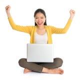 Brazos asiáticos de la muchacha para arriba usando el ordenador portátil Foto de archivo libre de regalías