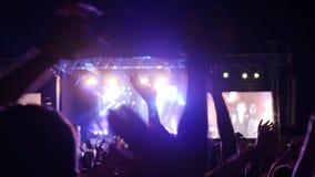 Brazos aumentados de gente en las luces brillantes en festival de la roca, fans que agitan las manos en el partido del concierto, almacen de metraje de vídeo