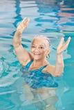 Brazos de elevación de la mujer mayor en clase de la aptitud de la aguamarina Foto de archivo libre de regalías